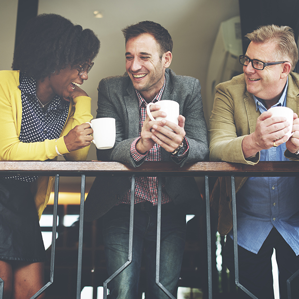 Three people standing together holding coffee cups and laughing