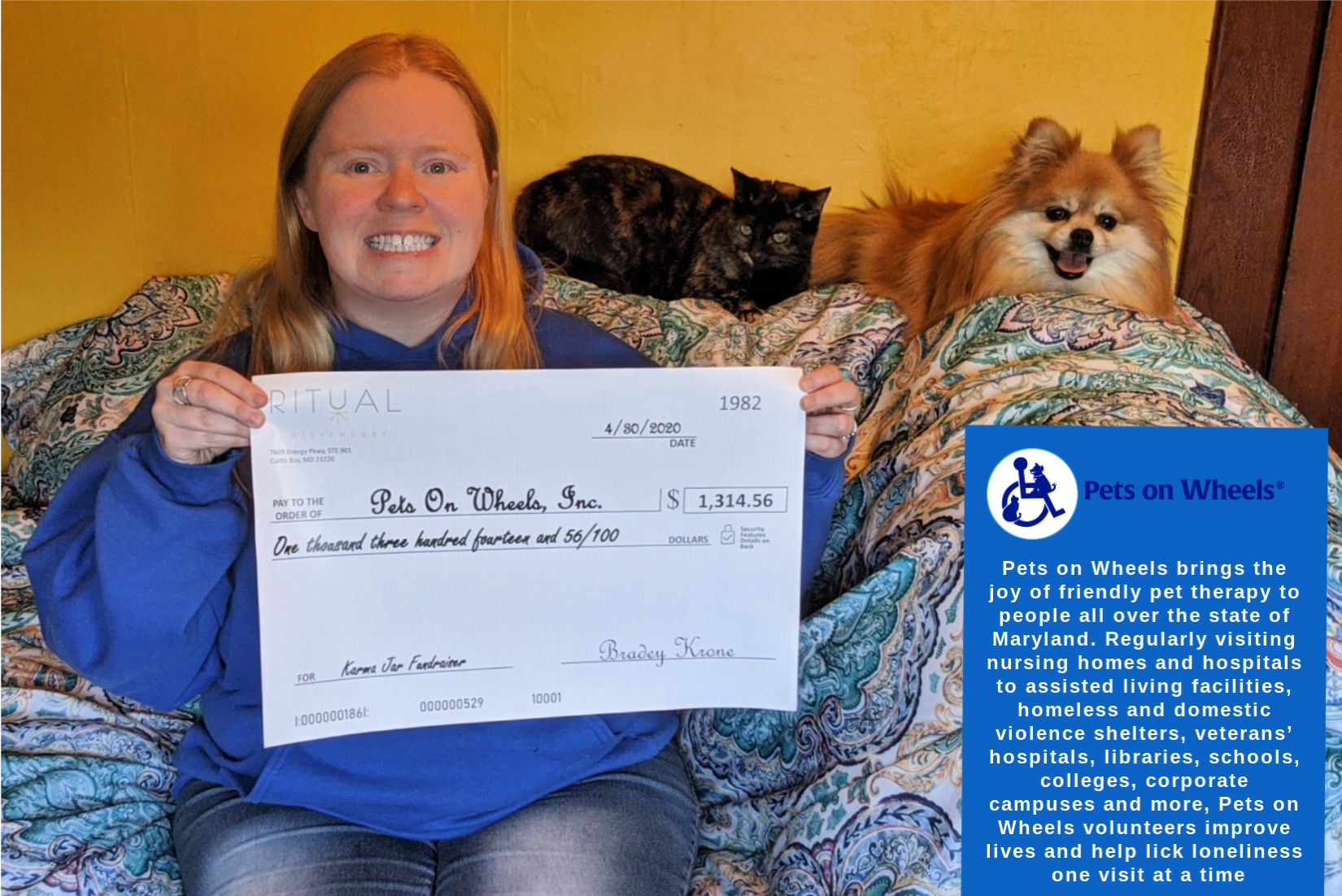 Ritual Pets on Wheels donation lady smiling with check with dog and cat in background