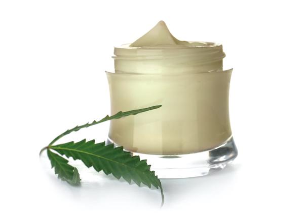 Jar of CBD cream with raw marijuana leaf