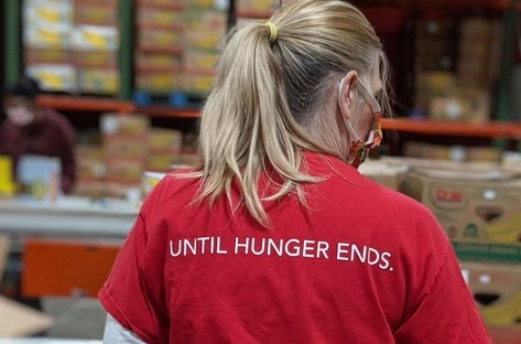 "Food bank volunteer with pony tail and red shirt that says ""Until Hunger Ends"" on back"